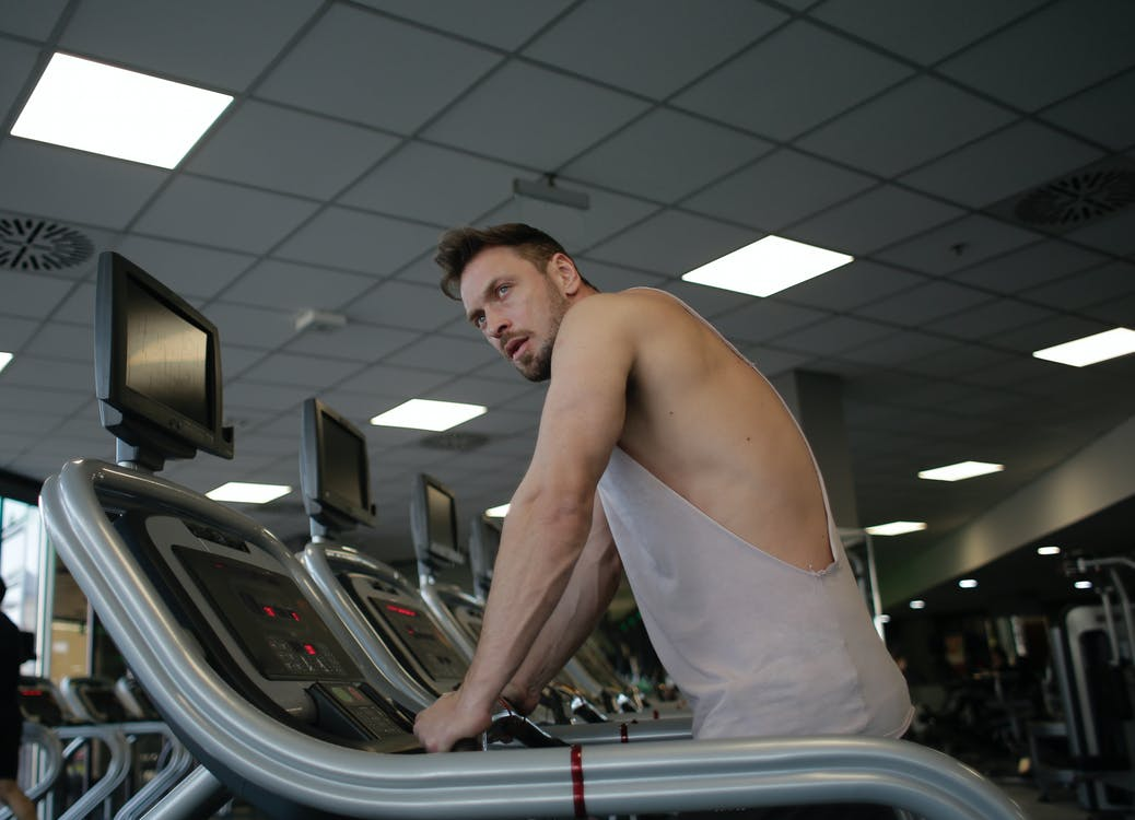 Man in White Tank Top Standing on Treadmill