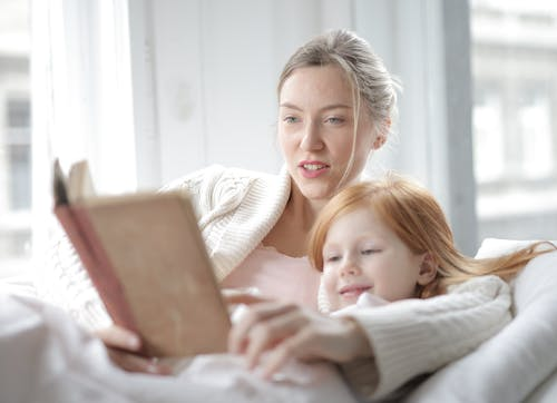 Woman in White Sweater Holding Book Lying Beside Girl
