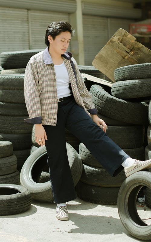 Photo Of Man Standing Near Tires