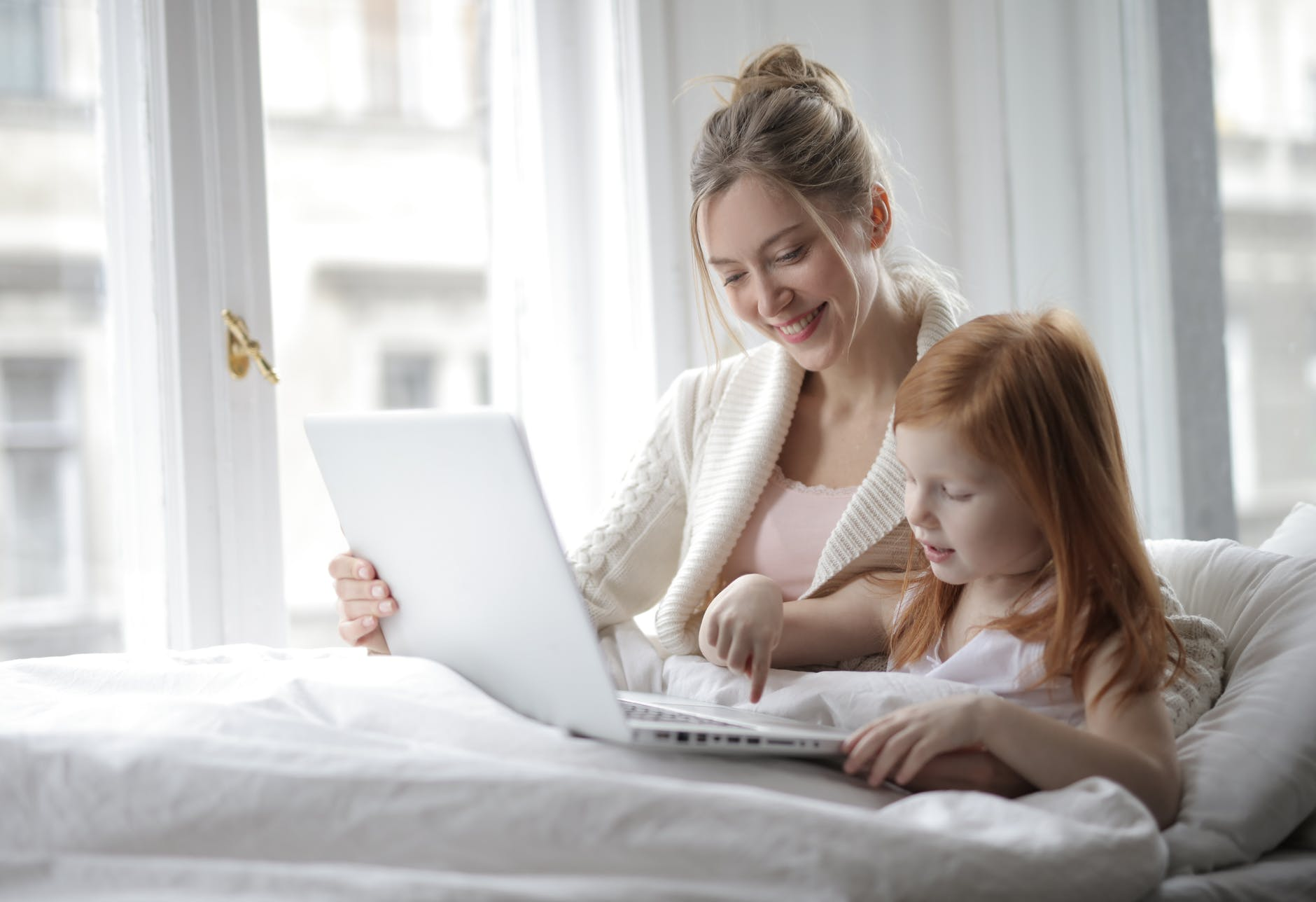 Mom and child looking at laptop under blanket
