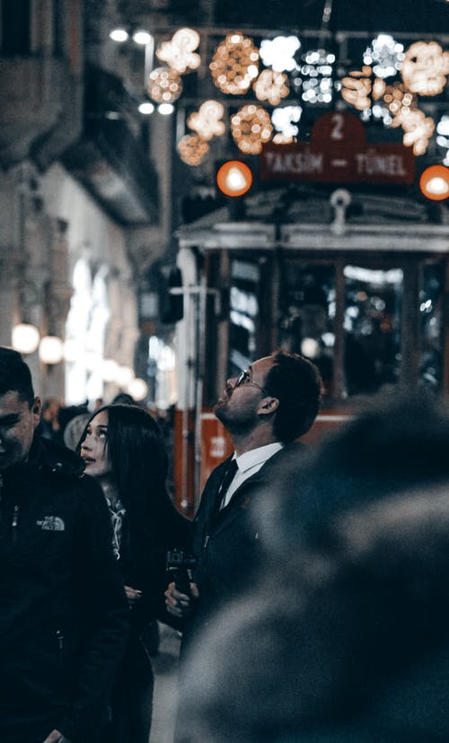 Couple standing on crowded street at night