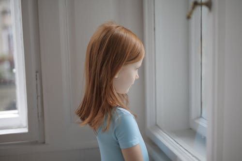 Girl in Blue T-shirt Looking Out the Window