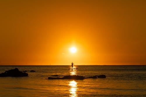 Silhouette of Person on Sea during Sunset