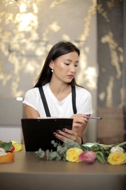 Focused young businesswoman counting daily sales in floral shop