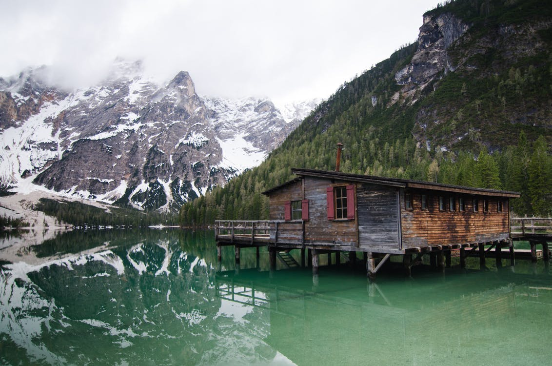 Brown Wooden House O Lake Near Snow Covered Mountain