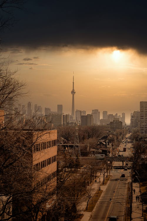 City Buildings Under Orange Sky During Sunset