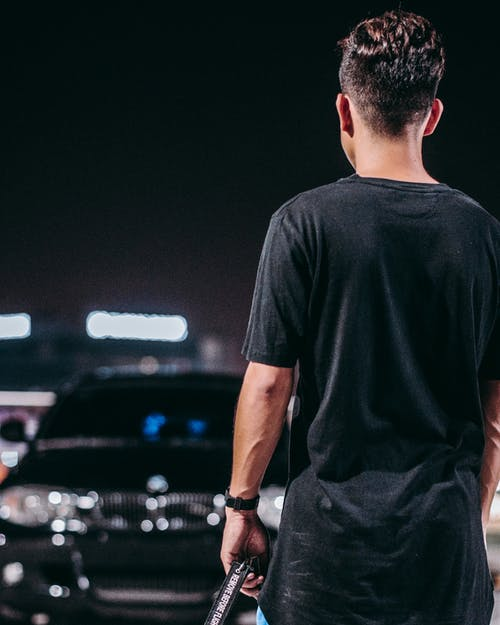 Man in Black Crew Neck T-shirt and Black Pants Standing on Parking Lot