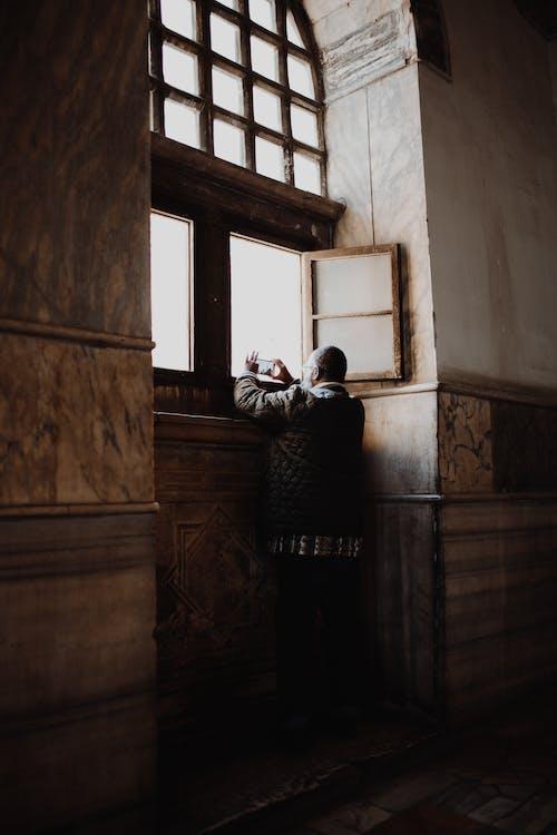 Person In Einer Jacke, Die Durch Das Fenster Steht, Das Fotos Macht