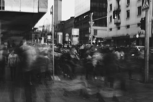 Grayscale Photo Of Blurry People Walking