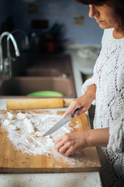 Person Slicing Dough on Brown Wooden Chopping Board