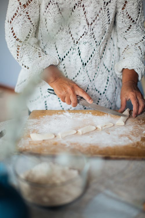 Person In Lace Top Slicing Dough