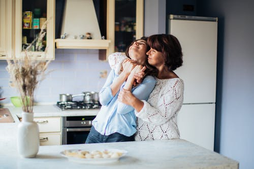 Woman In White Lace Long Sleeve Top Hugging Another Woman