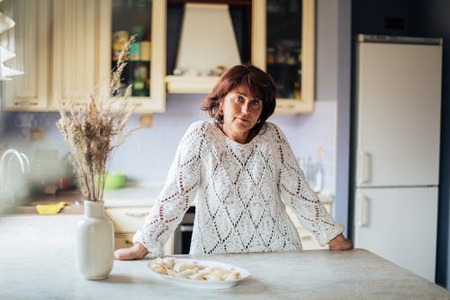 Woman in White Knit Sweater Standing at the Kitchen Counter