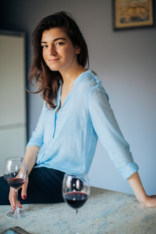 Photo Of Woman Sitting Near Wine Glass