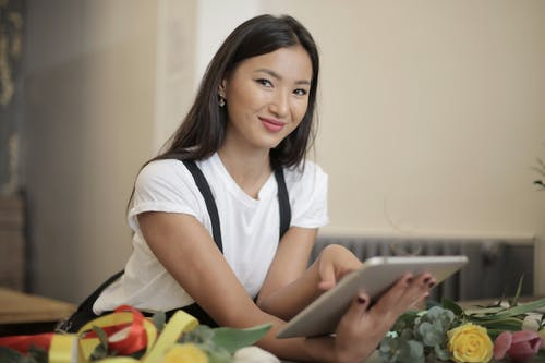 Woman in White T-shirt Holding Silver Tablet Computer