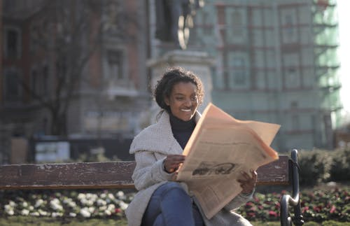 Woman in White Coat Sitting on Brown Wooden Bench Reading Newspaper