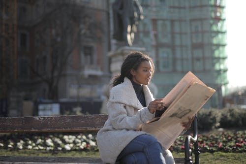 Woman in Gray Coat Sitting on Brown Wooden Bench Reading Newspaper