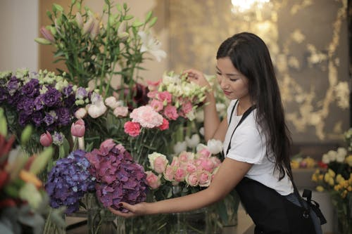 Woman in White Crew neck T-shirt Wearing Black Apron Holding Flowers