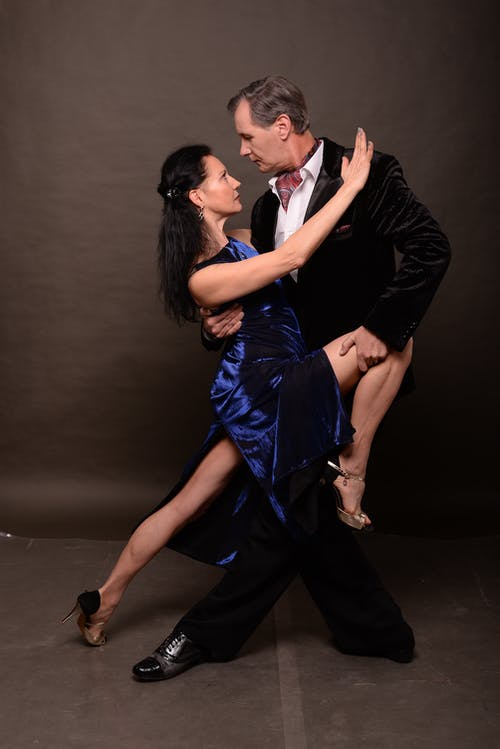 Man in Black Suit Dancing with Woman in Blue Dress