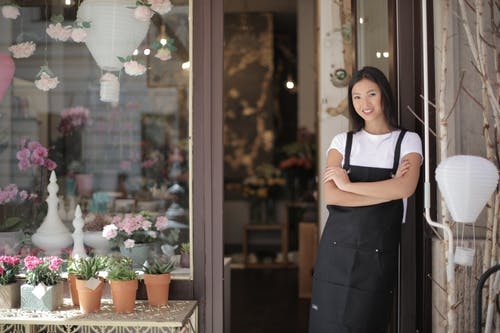 Woman in White Crew neck T-shirt Wearing Black Apron Leaning on Glass Door