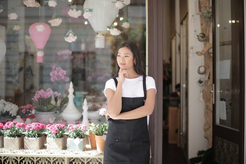 Woman in White Crew neck T-shirt Wearing Black Apron Leaning on Glass Window