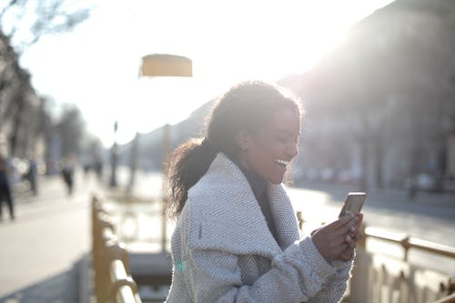 Selective Focus Photo of Woman in White Coat Holding Smartphone