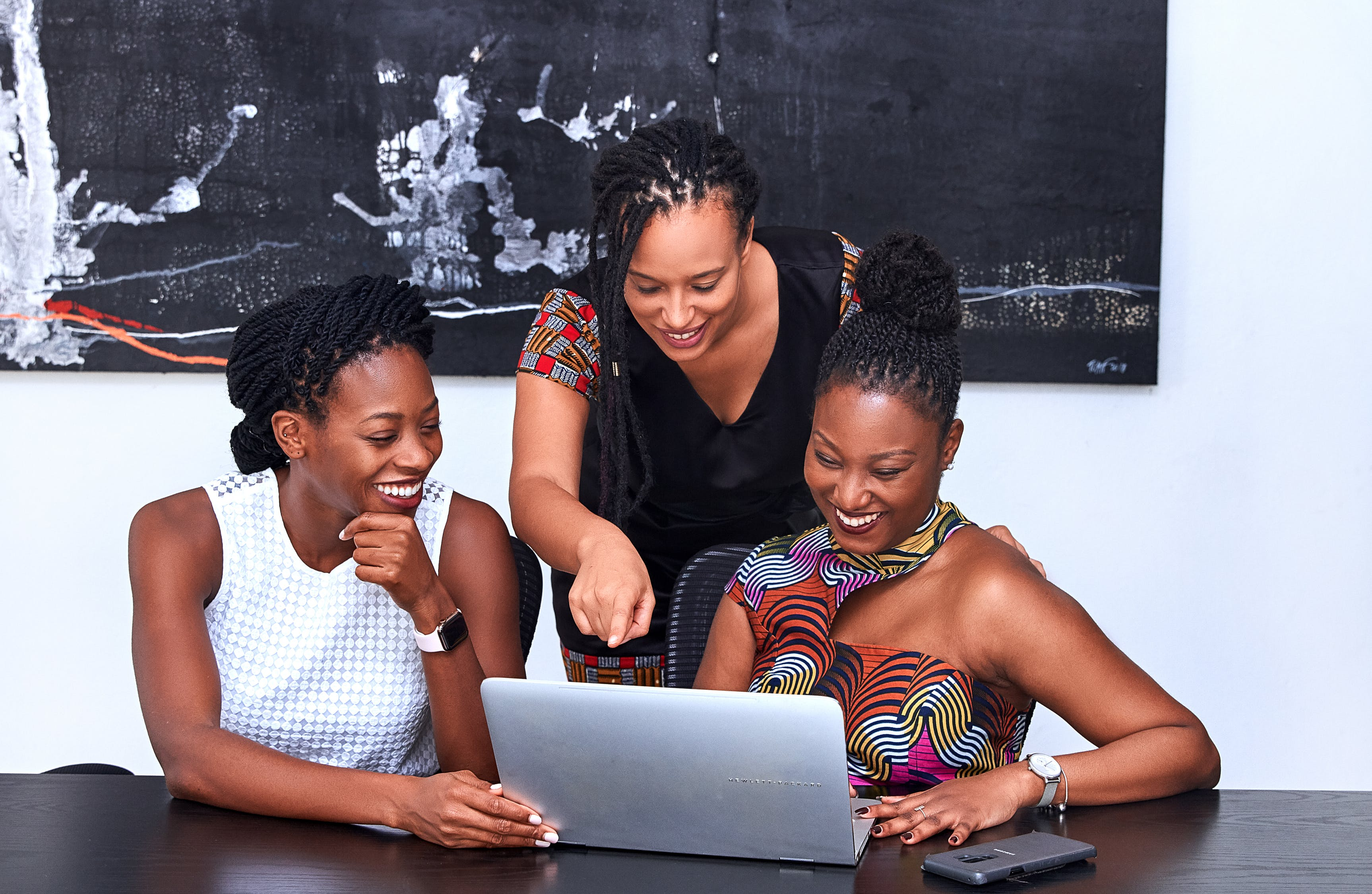 Three Black women crowded around at a laptop. They are all smiling and appear to be discussing something on the laptop screen.  Photo by PICHA Stock from Pexels