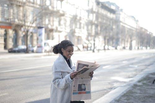Woman in White Coat Reading Newspaper on Sidewalk