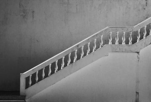 Grayscale Photo Of Concrete Staircase With Railings