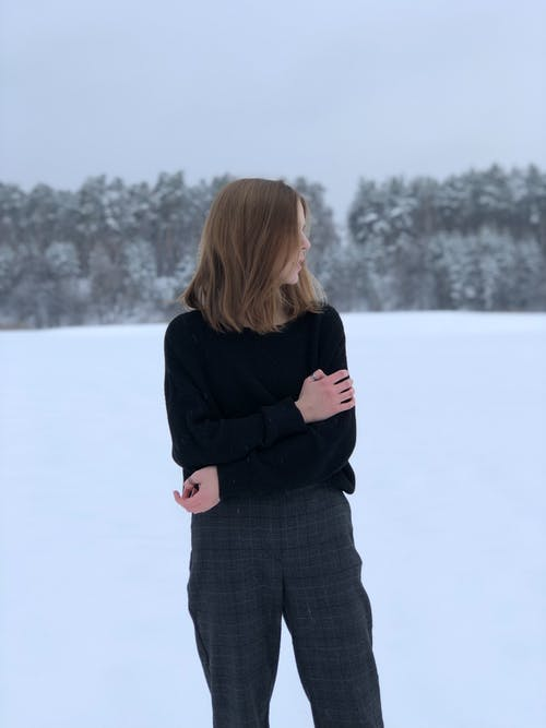 Woman in Black Sweater Standing on Snow Covered Ground