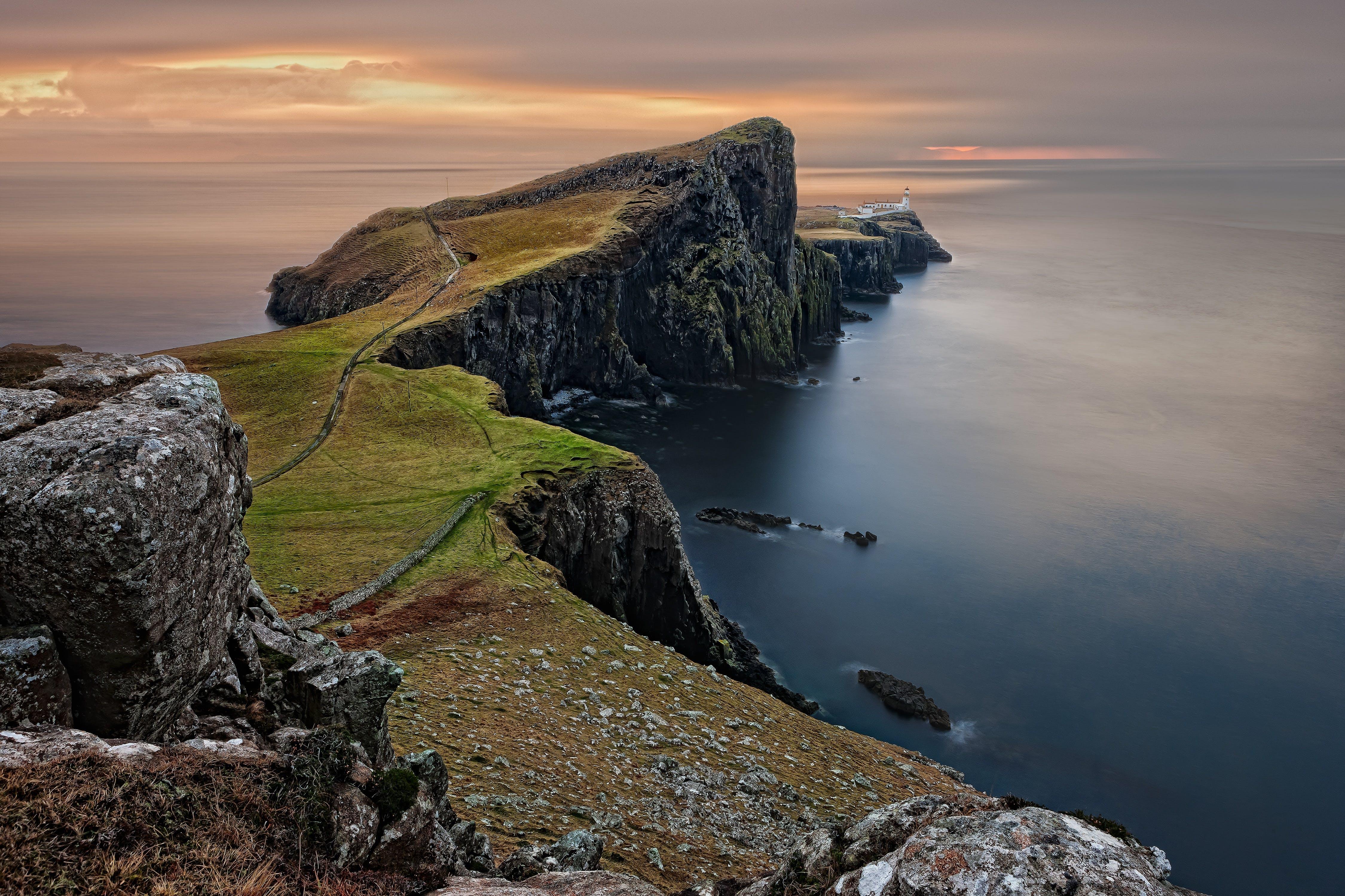 Green and Brown Mountain Cliffs Near Ocean