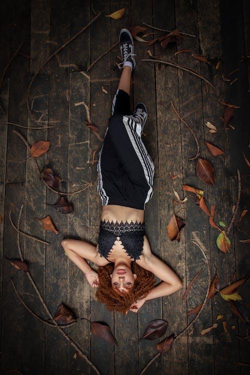 乾燥した葉に囲まれた床に横たわっている黒いクロップトップと黒いズボンの女性