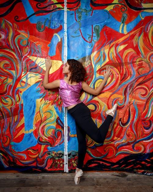 落書きで覆われた壁でポーズをとるバレリーナ