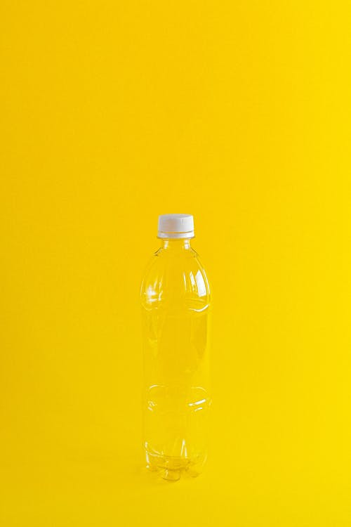 Clear Plastic Bottle Against Yellow Background
