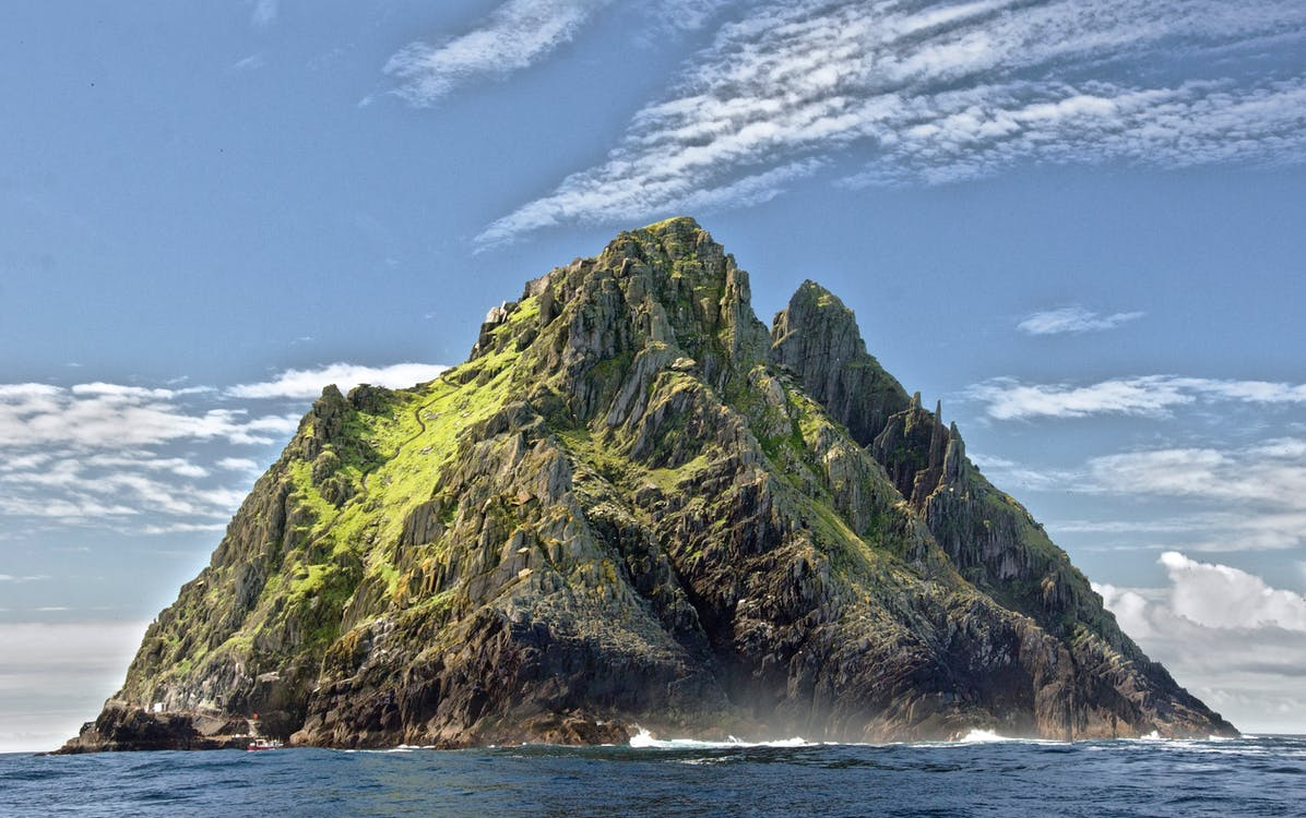 Green And Brown Mountain In The Middle Of The Ocean