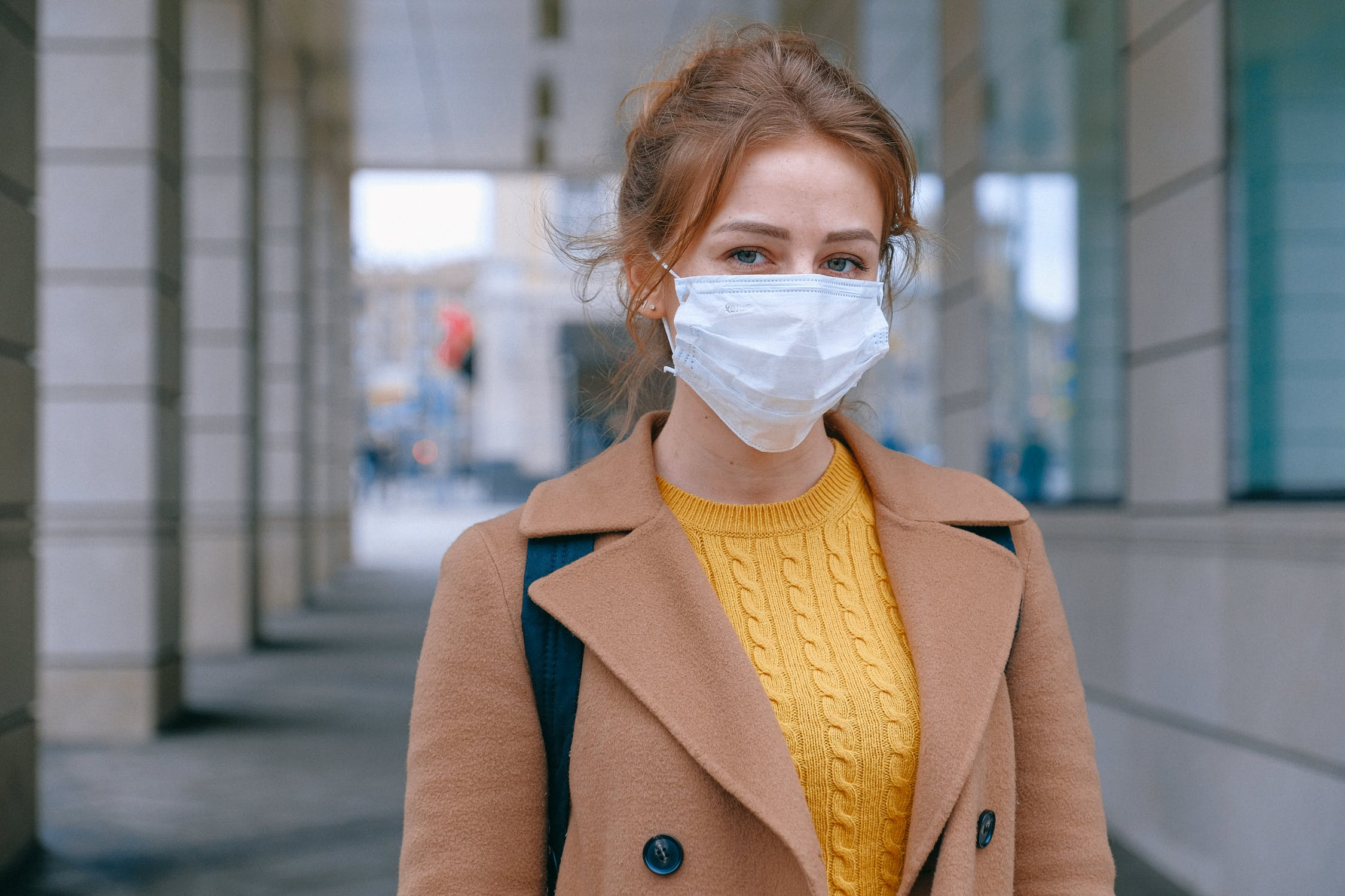 A woman standing under a building awning with a face mask on. Photo by pexels user Anna Shvets. Used courtesy of Pexels.com