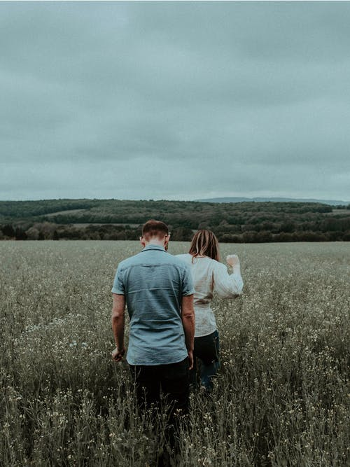 Man And Woman Walking On Green Grass Field