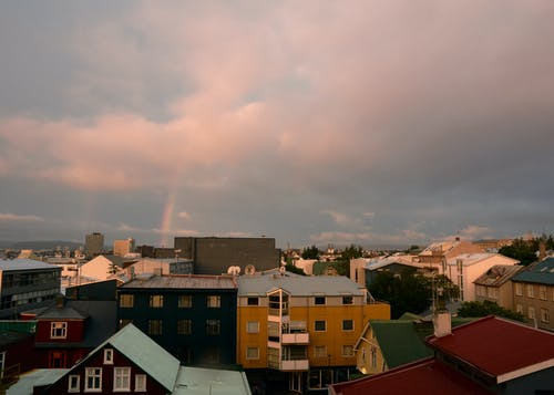 Small town under cloudy sky and rainbow