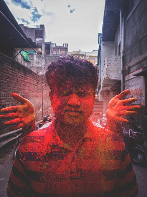 Ethnic man with closed eyes with palms behind throwing bright red paint during traditional Holi Festival