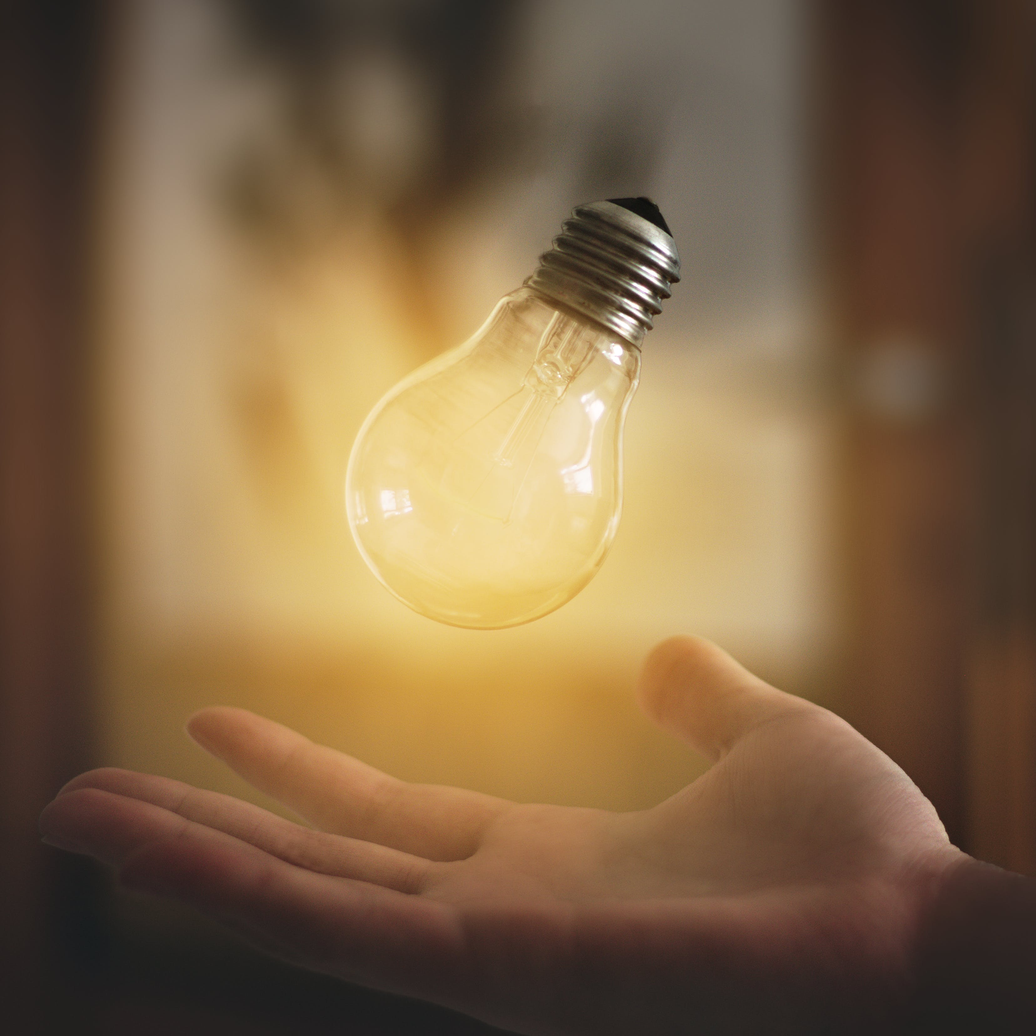 Light Bulb Floating Above Person's Hand