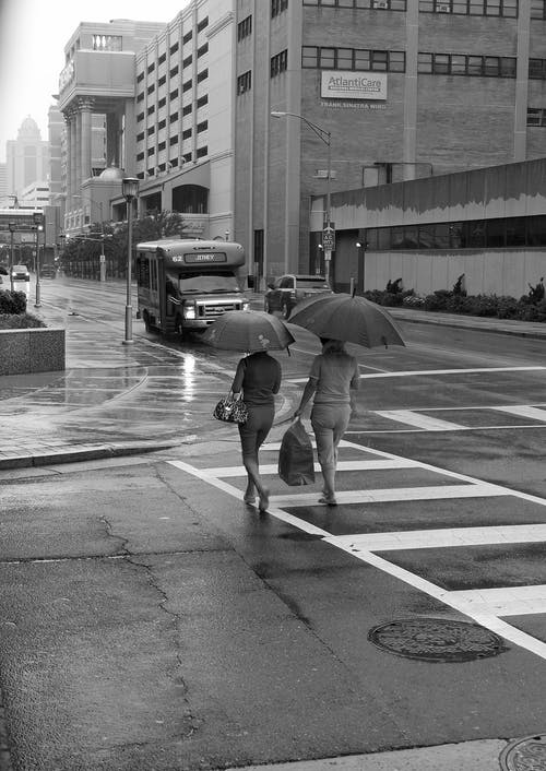 Grayscale Photo Of People Crossing The Road With Umbrella