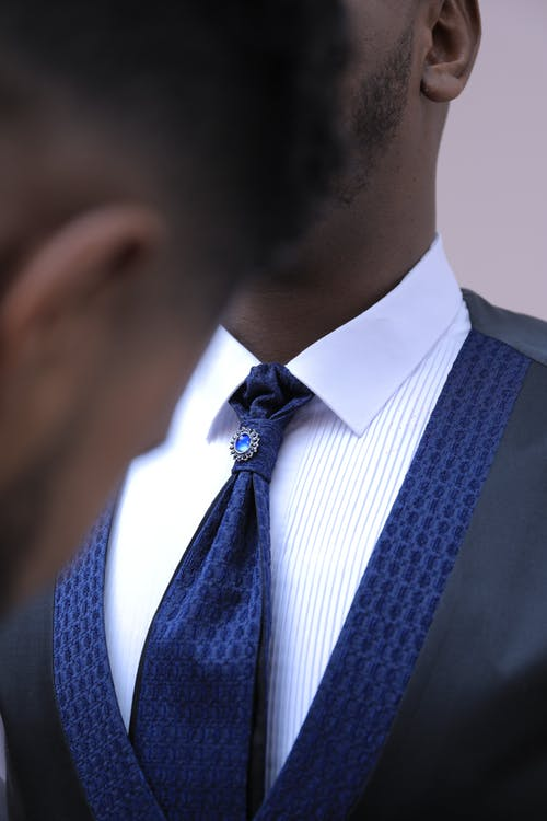 Crop anonymous African American man helping young friend in stylish elegant groom suit before wedding ceremony