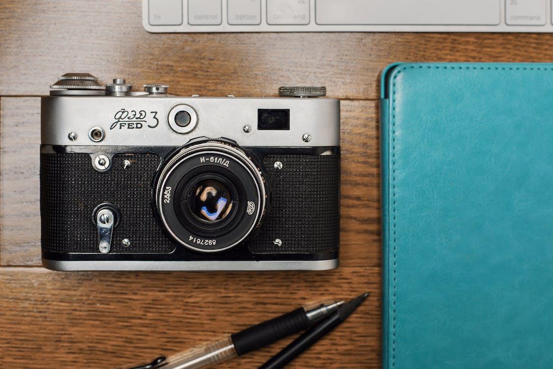 Câmera preta e prateada ao lado do estojo de couro azul