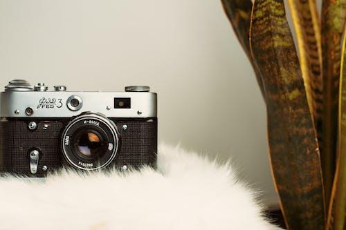 白色毛皮纺织上的黑色和银色相机