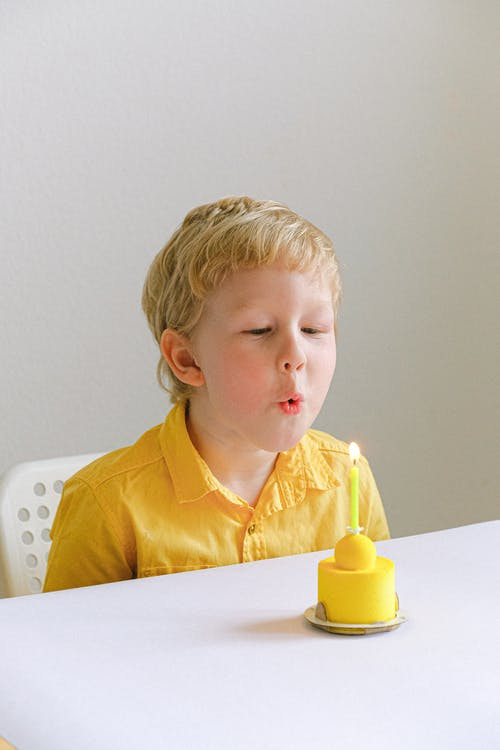 Boy In Yellow Polo Sitting On A Chair