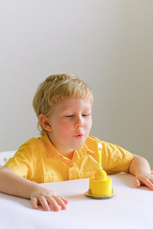 Boy In Yellow Polo Blowing A Candle