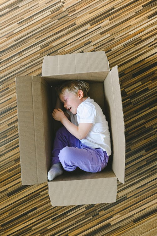 Boy In White T-shirt Inside A Box