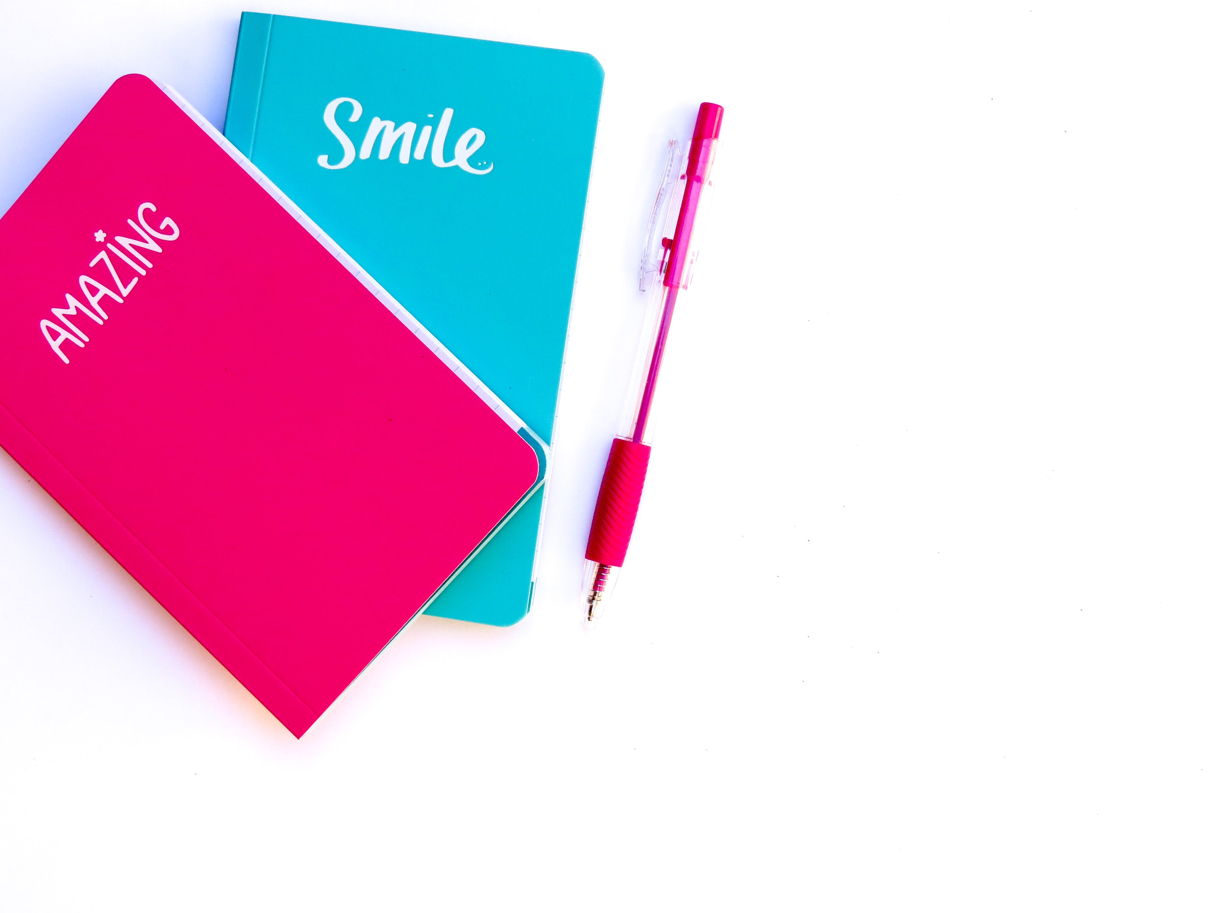 Pink and Blue Notebooks Beside Red Click Pen
