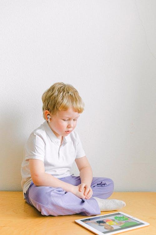 Boy In White Polo Shirt Sitting