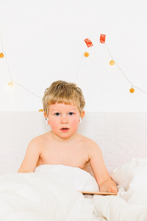 Topless Boy Sitting On White Bed